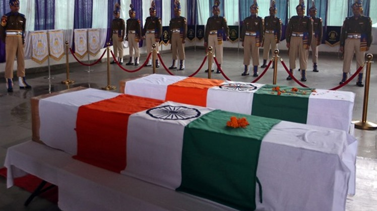 India's Central Reserve Police Force (CRPF) personnel stand behind the coffins of t district on Friday, during a wreath-laying ceremheir two colleagues, who according to police were killed during a gun battle with militants in north Kashmir's Kupwaraony